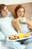 Os pares novos têm o pequeno almoço na cama Fotos de Stock Royalty Free