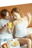 Os pares novos têm o pequeno almoço na cama Fotografia de Stock