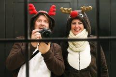 Os pares novos vestiram-se acima como a rena dois que toma um selfie Imagens de Stock