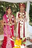Os pares nupciais hindu consideráveis novos no vestuário tradicional com cerimônia de casamento compõem Foto de Stock