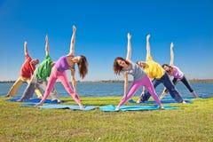 Os pares, o homem e a mulher da árvore praticam o asana da ioga na beira do lago. Imagens de Stock