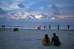 Os pares olham e famílias para jogar no crepúsculo na praia de Alleppey foto de stock royalty free