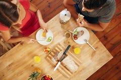 Os pares que apreciam uma manhã saudável tomam o café da manhã na cozinha Fotografia de Stock