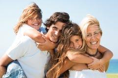 Os pares que dão crianças andam às cavalitas o sorriso dos passeios Fotos de Stock Royalty Free
