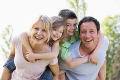 Os pares que dão duas crianças andam às cavalitas o sorriso dos passeios