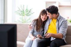 Os pares que olham a tevê em casa imagem de stock royalty free