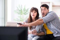 Os pares que olham a tevê em casa imagens de stock royalty free