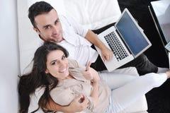 Os pares relaxam e trabalham no computador portátil em casa Fotografia de Stock Royalty Free
