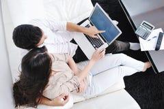 Os pares relaxam e trabalham no computador portátil em casa Fotos de Stock Royalty Free
