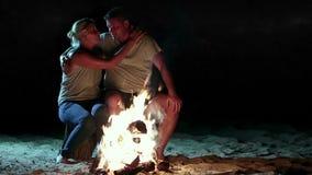 Os pares românticos aproximam o fogo na noite ao acampar video estoque