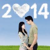 Os pares românticos com nuvens deram forma a 2014 Imagens de Stock Royalty Free