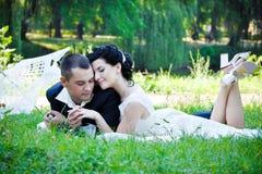 Os pares românticos com seus olhos fechados relaxam e beijam exterior no lago no parque do verde do verão Imagem de Stock Royalty Free