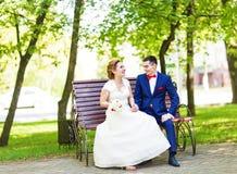 Os pares românticos do casamento que sentam-se em um banco estacionam na primavera fotos de stock