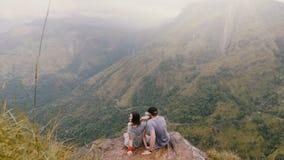 Os pares românticos felizes traseiros do recém-casado do ângulo alto da vista sentam-se junto sob a chuva no panorama épico da mo vídeos de arquivo