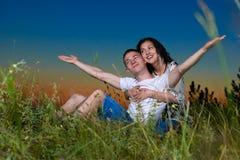 Os pares românticos novos abrem os braços e o divertimento ter no por do sol no céu noturno exterior, escuro, conceito da ternura Fotos de Stock Royalty Free