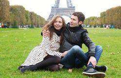 Os pares românticos novos aproximam a torre Eiffel foto de stock