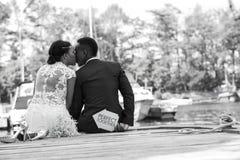 Os pares românticos que sentam-se em uma doca de madeira e expressam seu amor fotografia de stock royalty free