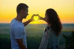 Os pares românticos no por do sol fazem uma forma do coração das mãos, dos raios do brilho do sol através das mãos, da paisagem b Imagens de Stock