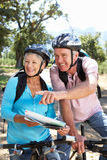 Os pares sênior com o mapa na bicicleta do país montam Imagens de Stock