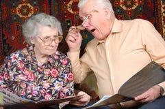Os pares sênior lêem a notícia e sorriem Fotografia de Stock Royalty Free