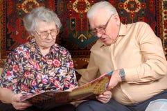 Os pares sênior leram a notícia Imagens de Stock Royalty Free