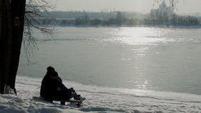 Os pares sentam-se no banco que admira a reflexão de raios do sol no rio no inverno vídeos de arquivo