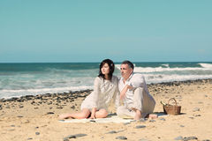 Os pares sentam-se para baixo na praia Imagens de Stock