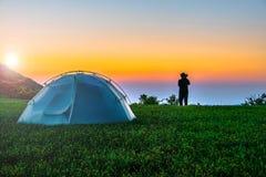 Os pares sentam-se perto da barraca de acampamento pelo fundo do nascer do sol do por do sol Grande ângulo fotografia de stock royalty free