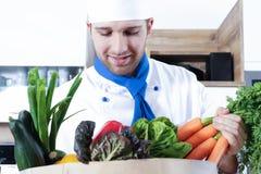 Os pares 'sexy' bonitos do homem da mulher como um cozinheiro estão cozinhando em uma cozinha foto de stock