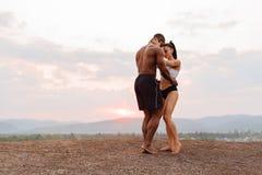 Os pares 'sexy' da raça misturada do ajuste com corpos perfeitos na dança do sportswear em montanhas ajardinam o fundo Fotografia de Stock