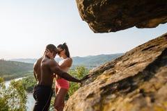 Os pares 'sexy' da raça misturada do ajuste com corpos perfeitos no sportswear que levanta nas montanhas rochosas ajardinam imagem de stock