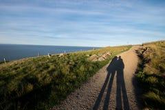 Os pares sombreiam na trilha de passeio litoral imagens de stock