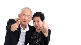 Os pares superiores asiáticos no negócio attire mostrar o thum do gesto de mão fotografia de stock royalty free