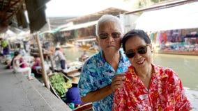 Os pares superiores asiáticos viajam ao mercado de flutuação de Tailândia Fotografia de Stock