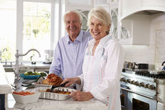 Os pares superiores fazem a refeição de Turquia do assado na cozinha junto imagens de stock