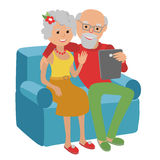 Os pares superiores felizes que sentam-se no sofá leram com tabuleta ilustração stock