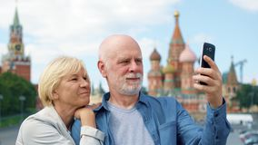 Os pares superiores na descida do ` s da manjericão fazem o selfie no telefone celular Curso dos pensionista em Moscou, Rússia vídeos de arquivo