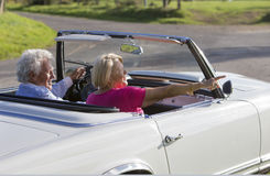 Os pares superiores no carro convertível do vintage que aprecia o dia tropeçam imagens de stock royalty free