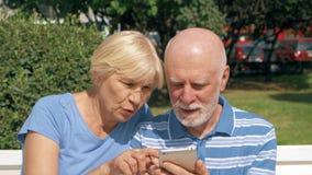 Os pares superiores sentam-se no banco no parque procuram o sentido através do app em linha com o mapa da cidade no telefone celu filme