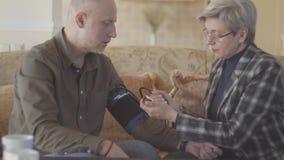 Os pares superiores sentam-se no sofá e a medição da mulher equipa a pressão sanguínea com dispositivo do tonometer S-log, ungrad vídeos de arquivo