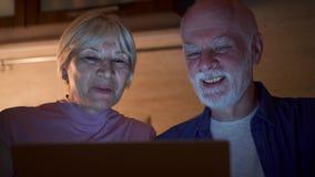 Os pares superiores têm em casa o bate-papo video no portátil através do mensageiro app Mãos da onda no cumprimento na noite filme