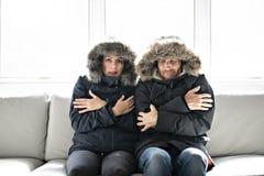 Os pares têm o frio no sofá em casa com revestimento do inverno foto de stock royalty free