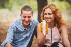 Os pares têm um piquenique na manta vermelha com frutos diferentes Imagens de Stock Royalty Free