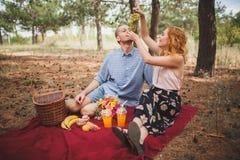 Os pares têm um piquenique na manta vermelha com frutos diferentes Fotos de Stock