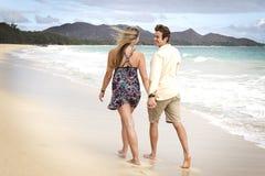 Os pares tomam uma caminhada na praia Fotografia de Stock Royalty Free
