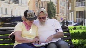 Os pares velhos à moda de viajantes sentam-se no banco na cidade estrangeira que olha o mapa vídeos de arquivo