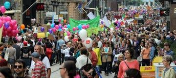 Os participantes da parada alegre levam bandeiras e balões de ar Fotos de Stock