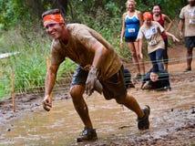 Os participantes da raça da lama que passam através de uma lama pit Imagem de Stock