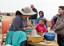Os participantes do festival ensinam a menina fazer o jarro da argila Foto de Stock Royalty Free