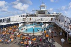Os passageiros apreciam um dia no mar na plataforma superior do navio de cruzeiros Fotos de Stock